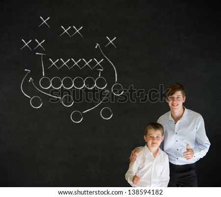 Thumbs up boy dressed up as business man with teacher man and chalk American football strategy on blackboard background - stock photo