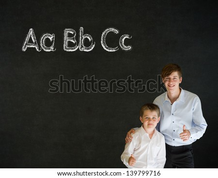 Thumbs up boy dressed up as business man with teacher man and learn English language alphabet on blackboard background - stock photo