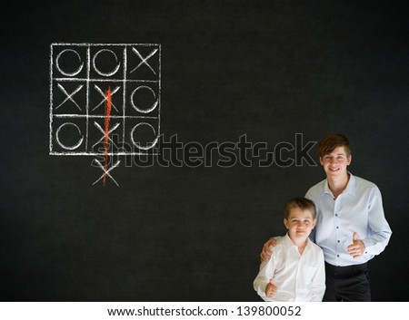 Thumbs up boy dressed up as business man with teacher man and thinking out of the box tic tac toe concept on blackboard background - stock photo