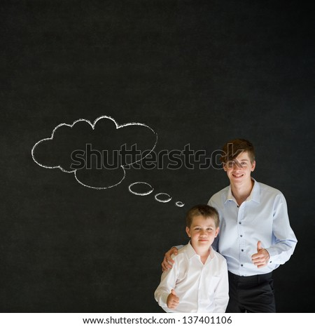 Thumbs up boy dressed up as business man with teacher man and thought thinking chalk cloud on blackboard background - stock photo