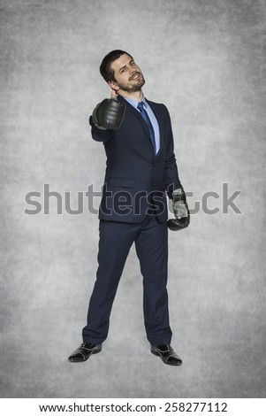 thumbs up businessman in boxing gloves - stock photo