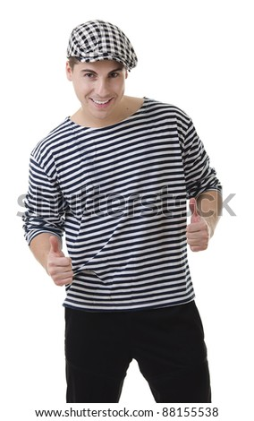 Thumbs up! by look naughty handsome young man in stylish striped dress and cap with suitcase