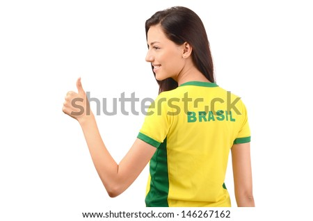 Thumbs up for Brazil. Attractive girl with Brazil written on her yellow t-shirt. Isolated on white. - stock photo