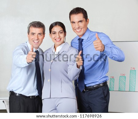 Thumbs up from successful business team in the office - stock photo
