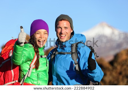 Thumbs up happy hikers hiking in mountain people. Cheering hiker couple looking at camera excited in mountain nature landscape. Woman and man on volcano Teide, Tenerife, Canary Islands, Spain - stock photo