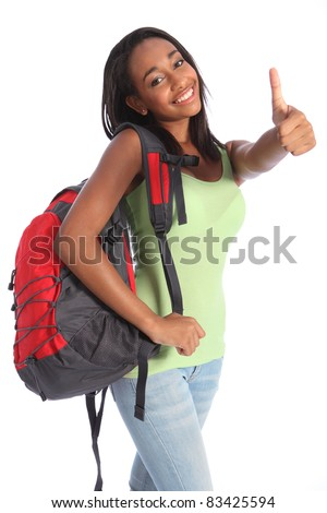 Thumbs up happy success for pretty young African American teenager school girl, with long black hair wearing green t-shirt and red school backpack with beautiful smile.