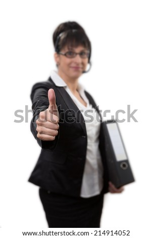 thumbs up woman in suit wearing a file and a headset while thumbs up with one hand - stock photo