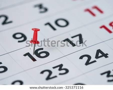 Thumbtack in calendar concept for important date, busy day, appointment or meeting reminder - stock photo