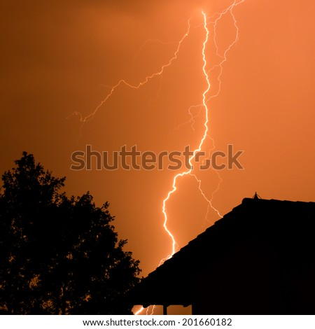Thunderbolt with tree and house - stock photo