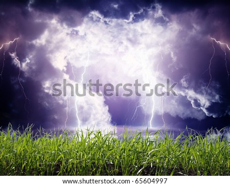 Thunderstorm with lightning in green meadow. - stock photo