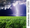 Thunderstorm with lightning in green meadow. Dark ominous clouds. - stock photo