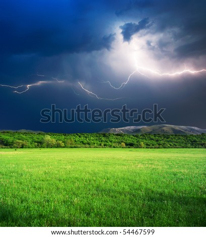 Thunderstorm with lightning  in green meadow. Nature composition. - stock photo