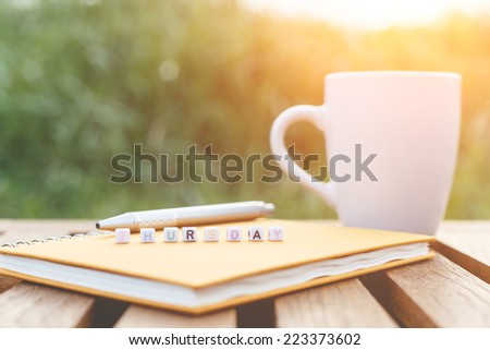 Thursday written in letter beads and a coffee cup on table - stock photo