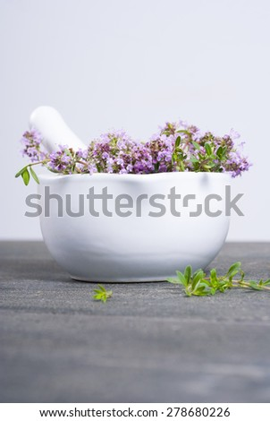 thyme flowers in a mortar on dark wood table - stock photo