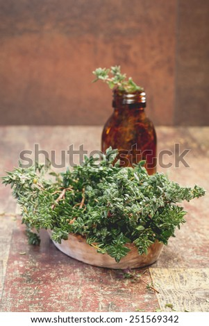Thyme. Fresh thyme herb and Essential thyme oil in a dark glass bottle with copy space for your text. A macro photograph with very shallow depth of field   - stock photo