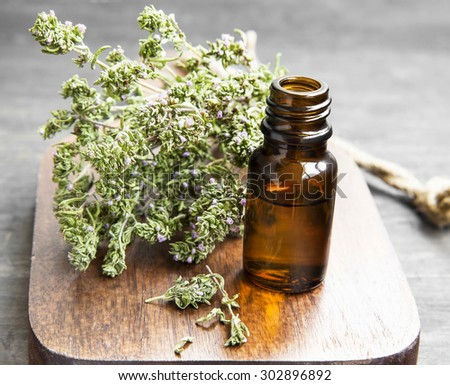 Thyme Herb Essential Oil Bottle on a Wooden Board - stock photo