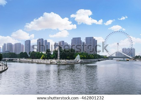 TIANJIN, CHINA - JUL 04, 2016: Tianjin is a metropolis in northern coastal China, tall giant Ferris wheel built above the Yongle Bridge, over the Hai River in Tianjin. JULY 04, 2016