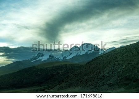 Tibet's snow-capped mountains at sunset - stock photo