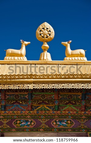 Tibetan Monastery Gates. Buddhist symbols: Dharma-wheel and deer on decorated roof under blue sky at Thiksey Gompa. India, Ladakh, Thiksey Monastery - stock photo