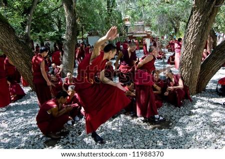 Tibetan monks at Sera monastery debating in the courtyard - stock photo