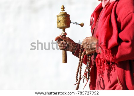 Tibetan prayer wheel in hand of old Bhutanese prayer, Thimphu, Bhutan. (Selective focus)