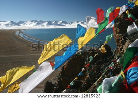 Tibetan Praying Flags with The Yamdrok Tso Lake and snowcapped mountain peaks in background. Tibet