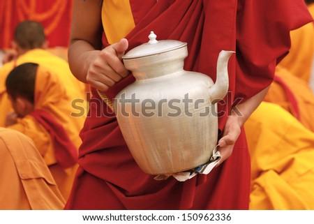Tibetan tea teapot in the hands of a monk in Nepal - stock photo