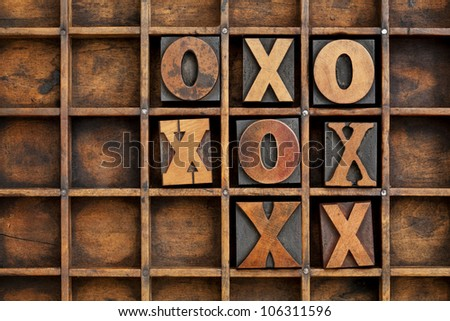 tic-tac-toe or noughts and crosses game - vintage letterpress printing block X and O in wooden grunge typesetter box with dividers - stock photo