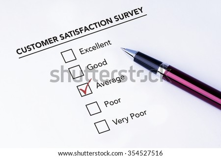 Tick placed in average check box on customer service satisfaction survey form with a pen on isolated white background. Business concept survey. - stock photo