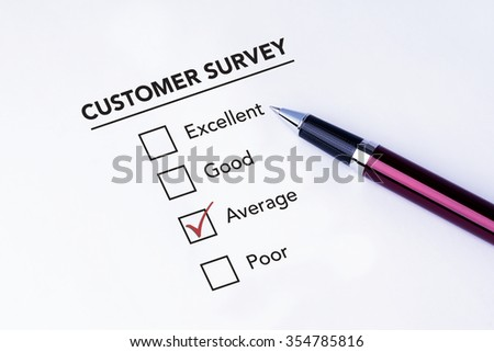 Tick placed in average check box on customer service satisfaction survey form with a pen on isolated white background. Business concept survey.