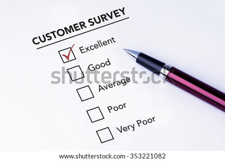 Tick placed in excellent checkbox on customer service satisfaction survey form with a pen on isolated white background. Business concept survey. - stock photo