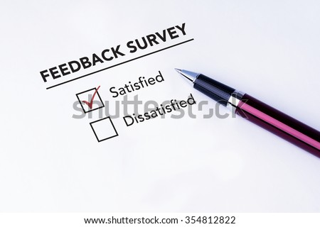 Tick placed in satisfied check box on feedback survey form with a pen on isolated white background. Business concept survey. - stock photo