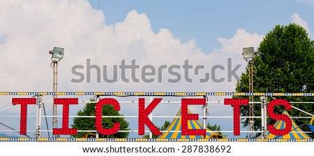 tickets classic electric sign like the ones used in circus or old fashioned shops, in the daylight with clouds and blue sky - stock photo