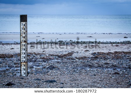 Tidal marker with a measurement scale to measure the depth of the incoming high tide implanted on a coastal beach to record flooding and natural disasters - stock photo