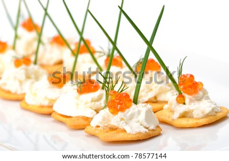Tidbits with cream cheese and trout kaviar - stock photo