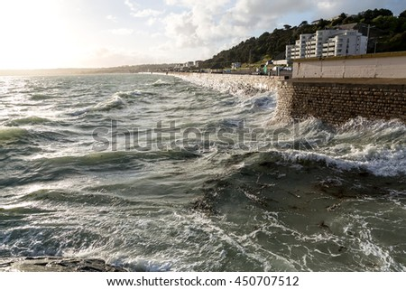 Tide and waves on the island of Jersey at sunset. - stock photo