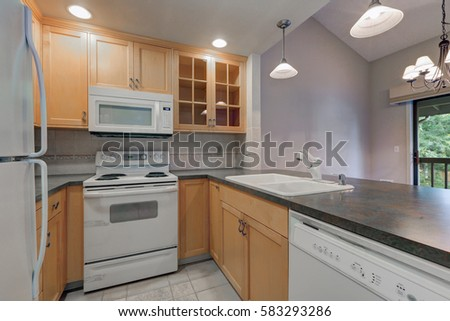 Tidy Compact Kitchen With Maple Cabinets, Dark Grey Counters, White  Appliances And Beige Tile