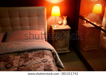 tidy romantic bedroom with red lamp