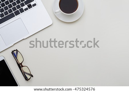 Tidy white office table with laptop, mobile phone, eyeglasses and a cup of coffee on it