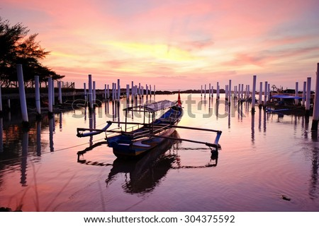 Tied boat and the sunset - stock photo