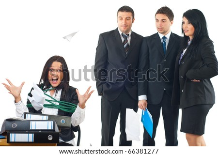 Tied business woman in a chair at desktop being furious and  throwing papers by much work while her colleagues looking with surprised faces  at her - stock photo