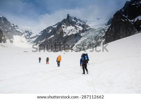 Tied climbers climbing mountain with snow field - stock photo