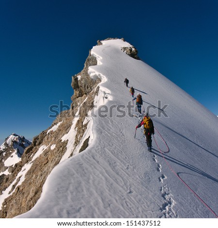 Tied climbers climbing mountain with snow field tied with a rope with ice axes and helmets - stock photo