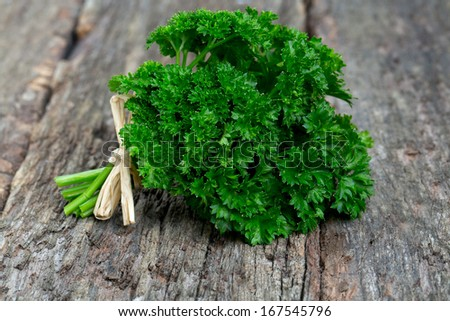tied fresh parsley on wooden surface - stock photo