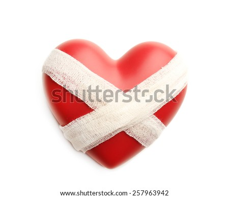 Tied heart with bandage isolated on white - stock photo