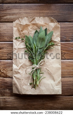 Tied sage leaves and herbs on a wooden background