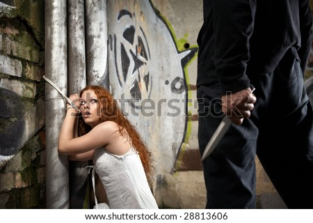 Tied woman is looking at a man with a knife - stock photo