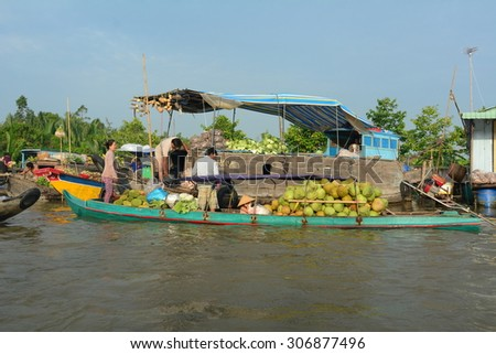 TIEN GIANG PROVINCE, VIETNAM - FEB 11, 2015: Flower vendors on their boats at Cai Be Floating Market. Cai Be Market is one of most famous floating market in Vietnam.