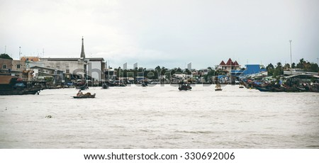 Tien Giang, Vietnam - Jan 20, 2014: Tien river scene in Mekong Delta, with rowing boats and church on background - stock photo