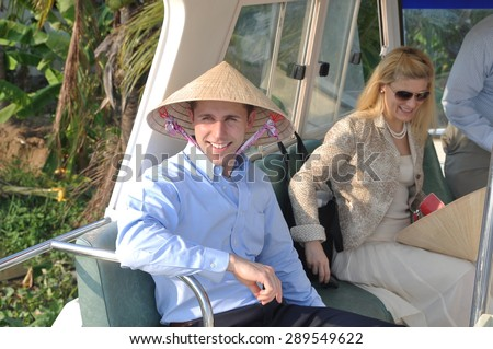 TIEN GIANG, VIETNAM - MARCH 29, 2013: A foreigner with a Vietnamese traditional hat is visitting the mekong delta of vietnam on a canoe - stock photo